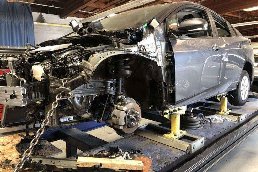Auto body repairs. Repairman mechanic worker plastering automobile car body by plaster in garage workshop